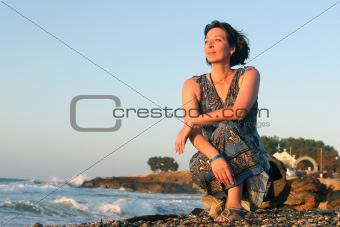 Greek woman in bluw sitting on a beach