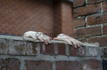 Someones hands gripping on to the top of a wall