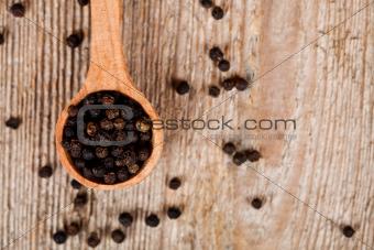 black peper in wooden spoon