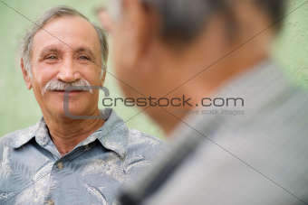 Two senior friends meeting and talking in park