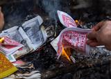 Burning fake dollars and dongs at the temple of One Pillar Pagod