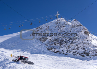 Chair lift and snow groomer