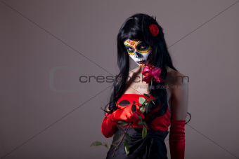 Sugar skull girl holding red rose