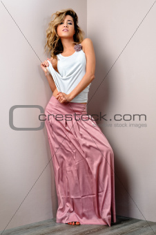 Portrait of a beautiful blonde woman in pink skirt.