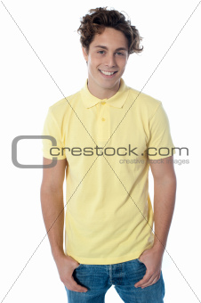 Portrait of a stylish guy standing with hands in pockets