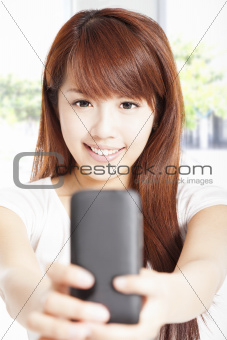 beautiful young woman holding and watching smart phone