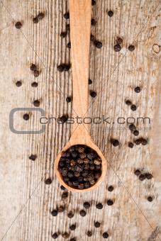 black pepper in wooden spoon