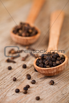 black pepper and cloves in wooden spoons