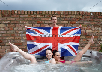 Three people with a union jack in a jacuzzi