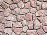 Red granite masonry wall closeup background.