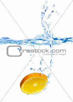 Fresh orange dropped into water with splash