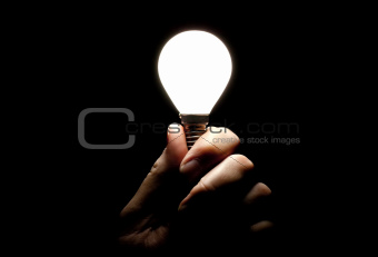 Lit lightbulb held in hand on black background