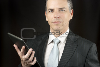 Confident Businessman Holds Tablet