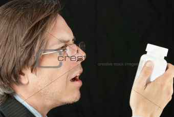 Casual Businessman Wearing Reading Glasses Trying To Read Pill B