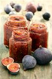 Figs and homemade jam in glass jars.