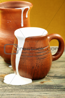 Ceramic mug with cream and clay jug.