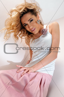 Portrait of the beautiful blonde woman in pink scirt.
