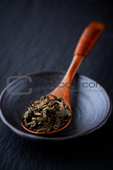 Green tea leaves on a bamboo spoon