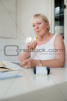 Mature woman checking bills and doing budget at home