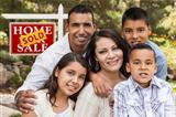 Happy Hispanic Family in Front of Sold Home for Sale Real Estate Sign.
