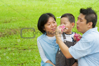 Asian family playing bubble wand