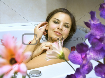 woman in a bath with flower petals