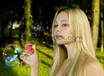 blonde blowing soap bubbles