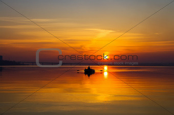 sunset over water surface with small boat