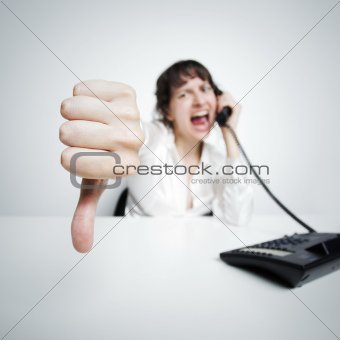 thumbs down against the camera by an hostile phoning businesswoman