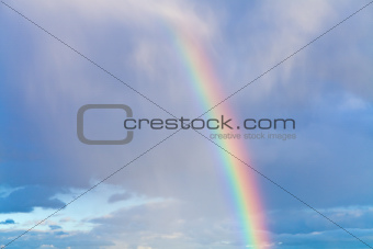 rainbow in blue cloudy sky