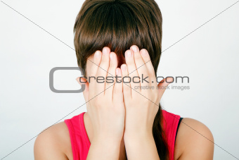 girl covers her face with both hands
