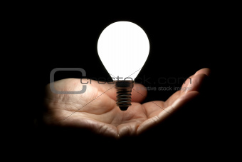 Floating lightbulb above hand on black background