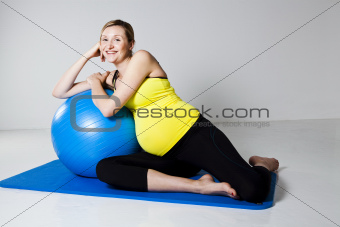 Pregnant woman relaxing against fitness ball
