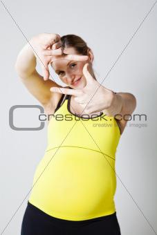 Pregnant woman making a frame