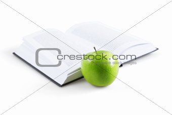art book and ripe green apple