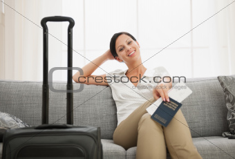 Smiling young woman with bag holding passport and air ticket