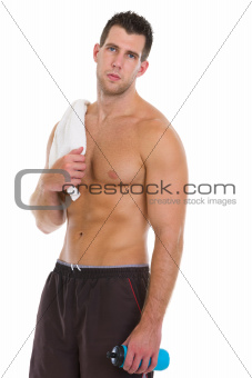 Healthy muscular man with towel and water bottle after workout