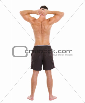 Sports man showing muscular body. Rear view