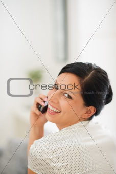 Portrait of happy young woman speaking mobile phone