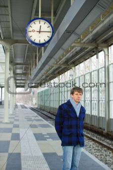 A man waiting for a train under a clock