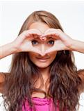 young girl looking through a heart shape formed by her fingers - isolated on white