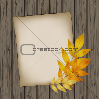 Paper sheet with autumn leaves on wooden background texture.
