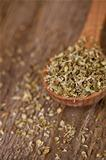 dry oregano in wooden spoon