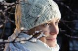 blue-eyed woman in white in the winter forest.