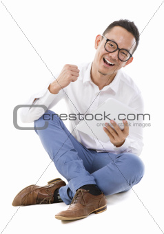Asian man sitting on floor using tablet