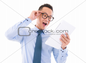 Surprise Asian business man looking at tablet