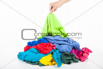 hand pick up a shirt in pile of colorful clothes