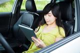 Young woman using tablet pc in the car