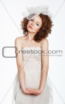 Curly sensual girl in white dress with bow