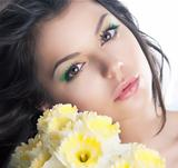 Cute brunette girl with flowers narcissus. Holidays